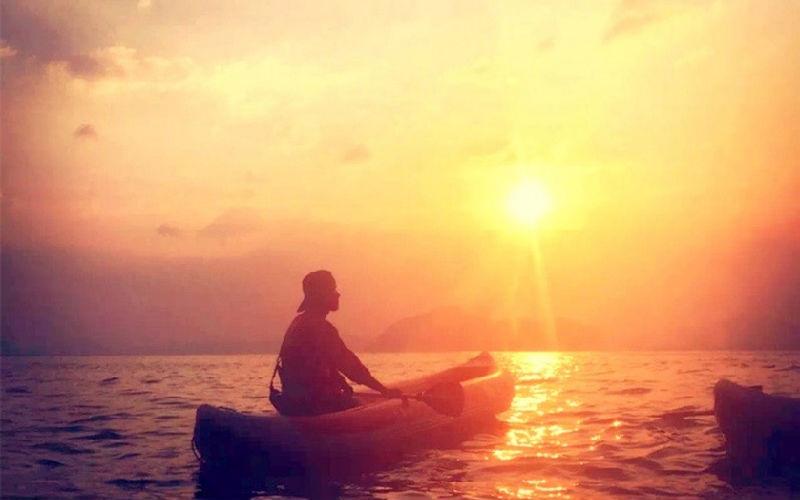 Kayaking and swimming under sunset.