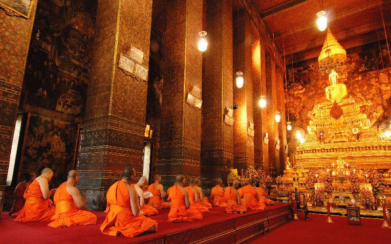 Picture: Beautiful golden buddha statue and monks in Wat Pho Temple.